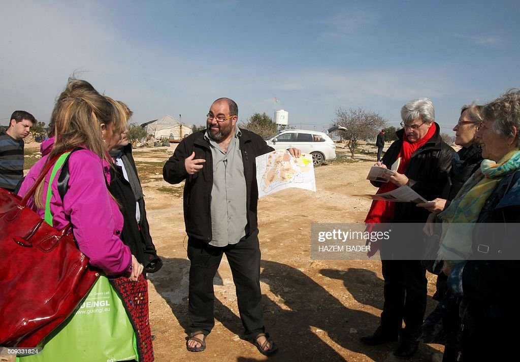 Yehuda Shaul (C), from the Israeli NGO Breaking the Silence, talks to members of the European Parliament during a visit to the Palestinian village of Susya, south-east of Hebron, in the Israeli-occupied West Bank, on February 10, 2016. Israel's High Court ruled in May 2015 that Susya's 340 residents could be relocated and its structures demolished, which Human Rights Watch derided as 'a grave breach' of Israel's obligations to the Palestinian populace under its military rule. / AFP / HAZEM BADER