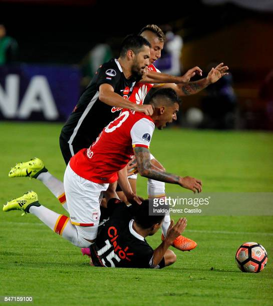 Yeison Gordillo of Santa Fe and Angel Cardozo fight for the ball with Antonio Bareira of Libertad during a second leg match between Independiente...