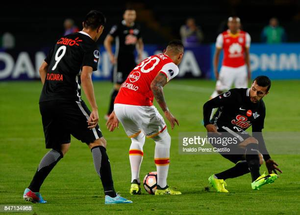 Yeison Gordillo of Santa Fe and Antonio Bareiro of Libertad compete for the ball during a second leg match between Independiente Santa Fe and...