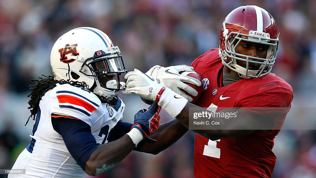 T.J. Yeldon #4 of the Alabama Crimson Tide breaks a tackle by T'Sharvan Bell #22 of the Auburn Tigers at Bryant-Denny Stadium on November 24, 2012 in Tuscaloosa, Alabama.