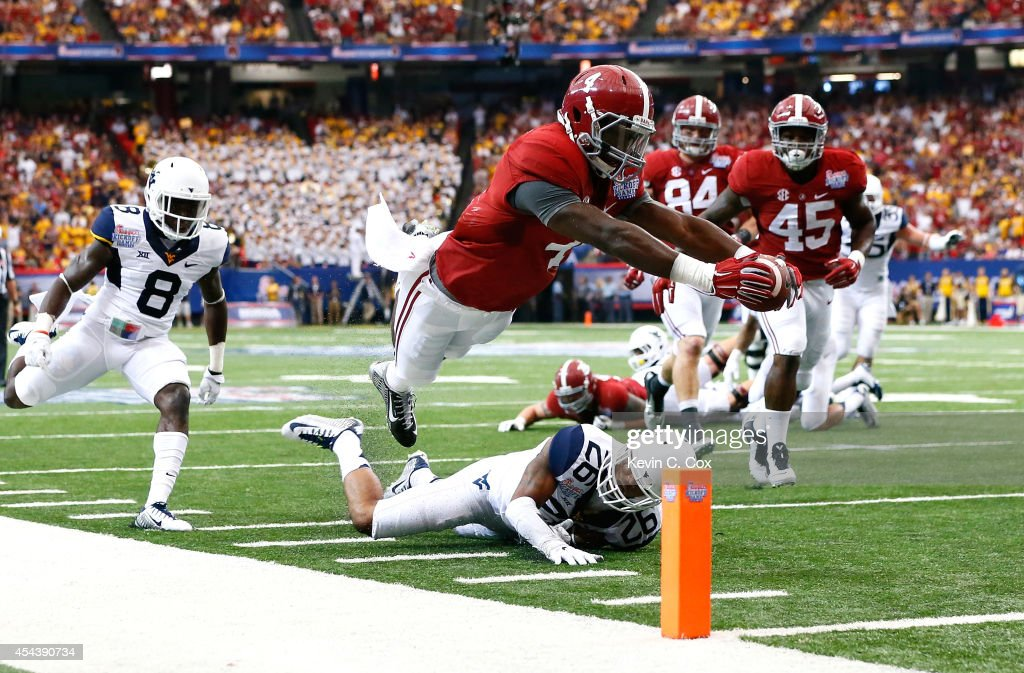 <a gi-track='captionPersonalityLinkClicked' href=/galleries/search?phrase=T.J.+Yeldon&family=editorial&specificpeople=9688955 ng-click='$event.stopPropagation()'>T.J. Yeldon</a> #4 of the Alabama Crimson Tide dives for a touchdown against Travis Bell #26 of the West Virginia Mountaineers at Georgia Dome on August 30, 2014 in Atlanta, Georgia.