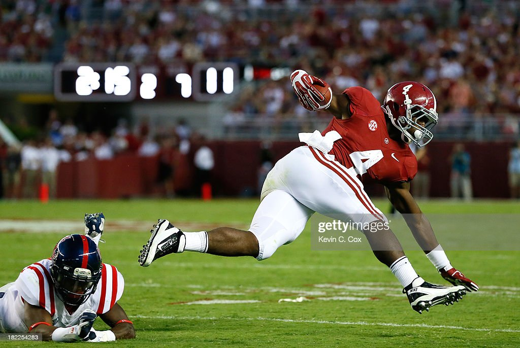 <a gi-track='captionPersonalityLinkClicked' href=/galleries/search?phrase=T.J.+Yeldon&family=editorial&specificpeople=9688955 ng-click='$event.stopPropagation()'>T.J. Yeldon</a> #4 of the Alabama Crimson Tide leaps over Mike Hilton #28 of the Mississippi Rebels at Bryant-Denny Stadium on September 28, 2013 in Tuscaloosa, Alabama.