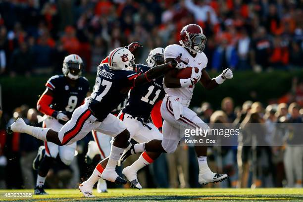 J Yeldon of the Alabama Crimson Tide runs the ball against the defense of Robenson Therezie and Chris Davis of the Auburn Tigers in the first quarter...