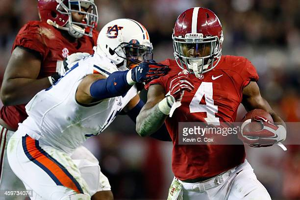 J Yeldon of the Alabama Crimson Tide runs the ball in the fourth quarter against the Auburn Tigers during the Iron Bowl at BryantDenny Stadium on...