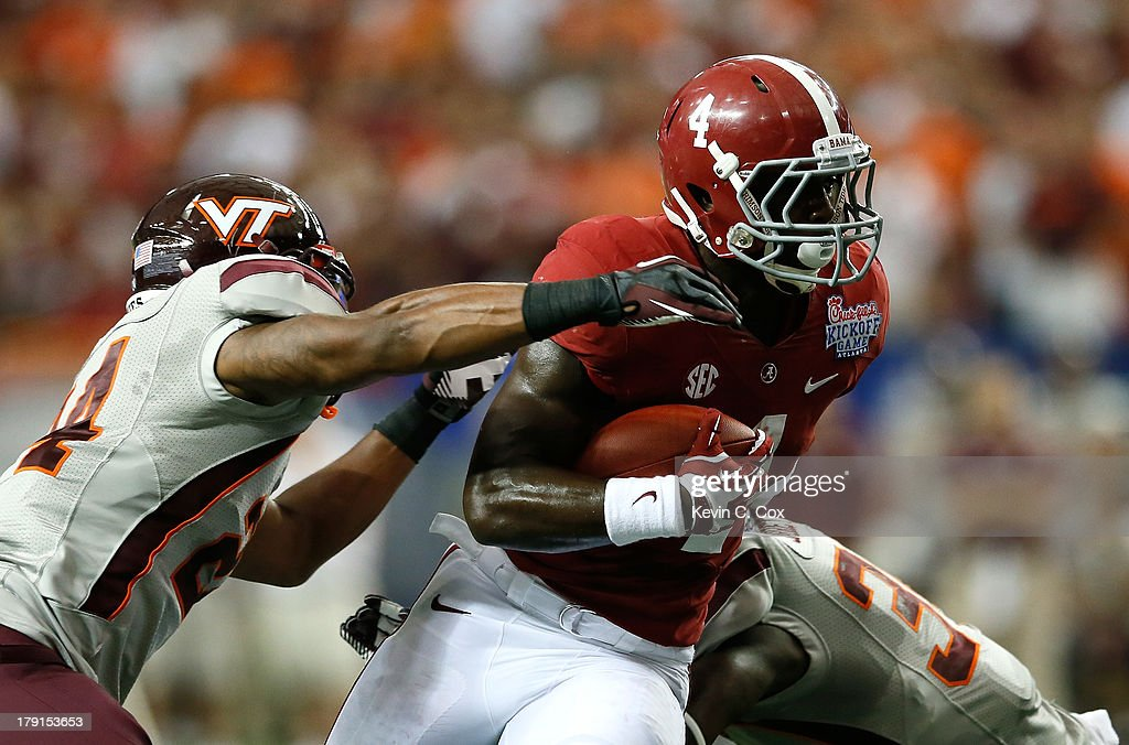 <a gi-track='captionPersonalityLinkClicked' href=/galleries/search?phrase=T.J.+Yeldon&family=editorial&specificpeople=9688955 ng-click='$event.stopPropagation()'>T.J. Yeldon</a> #4 of the Alabama Crimson Tide rushes between Tariq Edwards #24 and Kyshoen Jarrett #34 of the Virginia Tech Hokies at Georgia Dome on August 31, 2013 in Atlanta, Georgia.