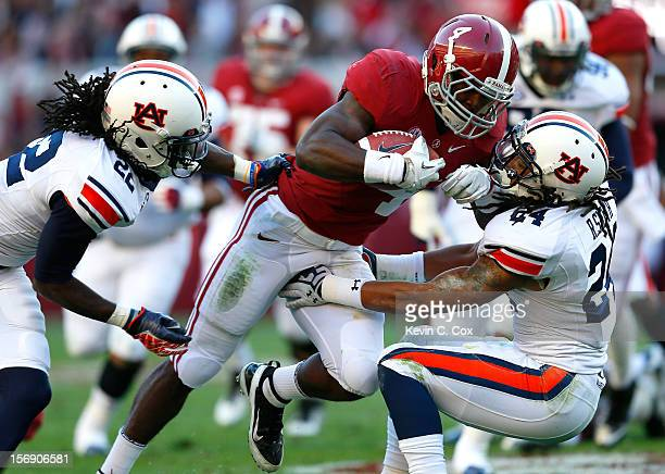 J Yeldon of the Alabama Crimson Tide rushes over T'Sharvan Bell and Ryan Smith of the Auburn Tigers at BryantDenny Stadium on November 24 2012 in...