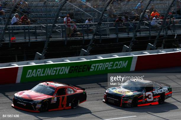 Yeley driver of the TriStar Motorsports Toyota leads Ty Dillon driver of the Bass Pro Shops/Tracker Boats Chevrolet during the NASCAR XFINITY Series...