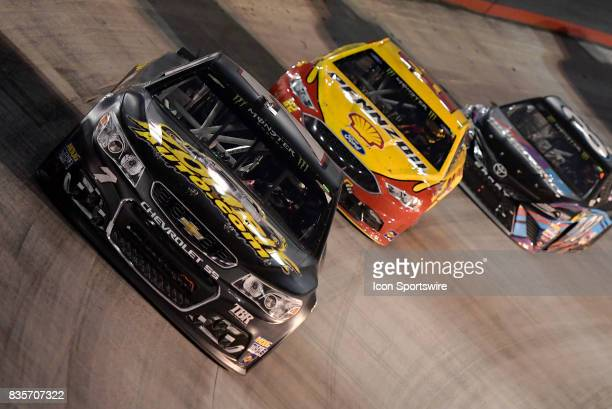Yeley Tommy Baldwin Jr Chevrolet SS is chased by Joey Logano Team Penske Ford Fusion into turn four during the Bass Pro Shops NRA Night Race on...