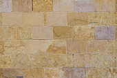 close up yellow aged sandstone brick wall background