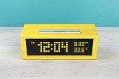 Yellow digital alarm clock on wood nightstand
