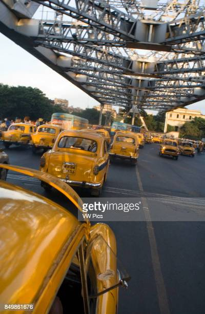 Yellow Ambassador taxis crossing Howrah Bridge in Kokata India Kolkata West Bengal India The taxi is one of the few nostalgic icons that represent...