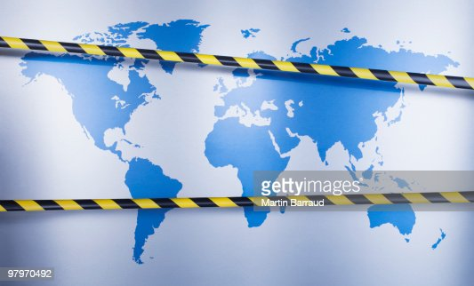 Yellow and black barricade tape over world map : Stock Photo