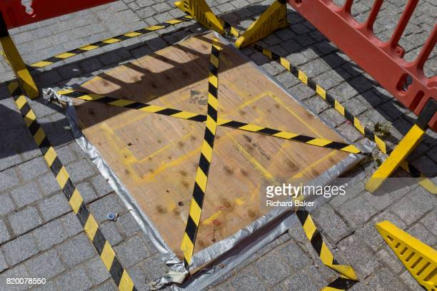 Yellow and black hazard tape on the ground of the pavement in Jubilee Gardens on 20th July 2017 on the Southbank London England
