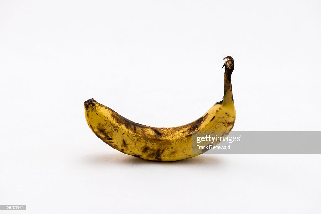 A yellow and black over ripe banana displayed on a white table