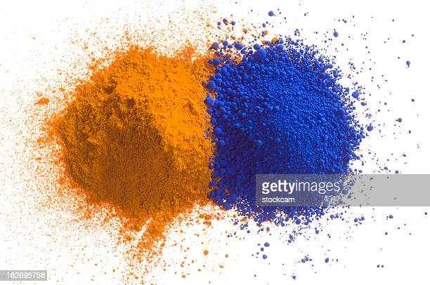 Yellow and blue piles of pigment powder on white