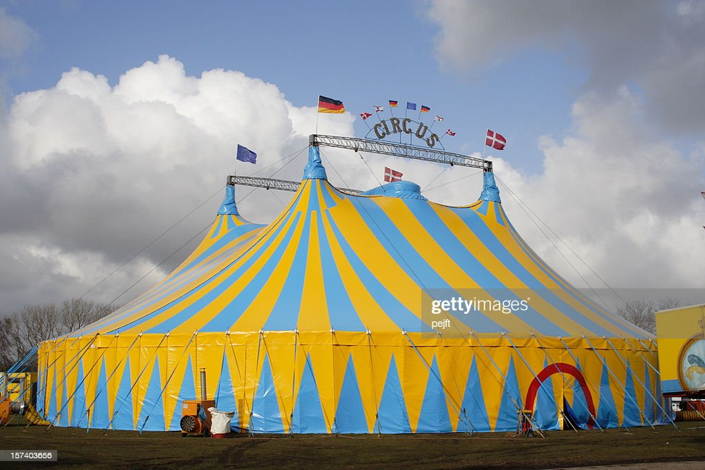 Yellow and light blue circus tent over a cloudy sky : Stock Photo
