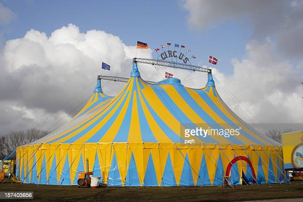 Yellow and light blue circus tent over a cloudy sky