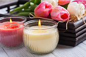 Yellow and pink aroma candles with tulips in dark wooden oriental box. SPA composition