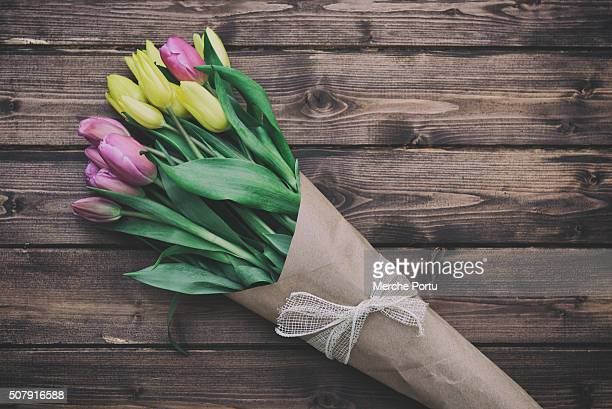 Yellow and pink tulips on wooden table