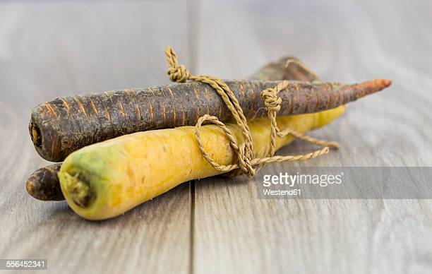 Yellow and prple carrots, organic vegetables on wood