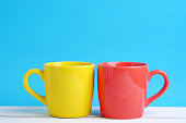 Close up of two cup yellow and red on white wood table and blue background concept, with blank space.