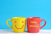 Close up of two cup yellow and red on white wood table and blue background concept. Happy monday idea.