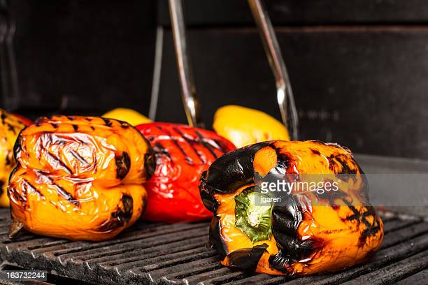 Yellow and red peppers roasting on a grill