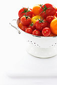 Yellow and red tomatoes in metal strainer