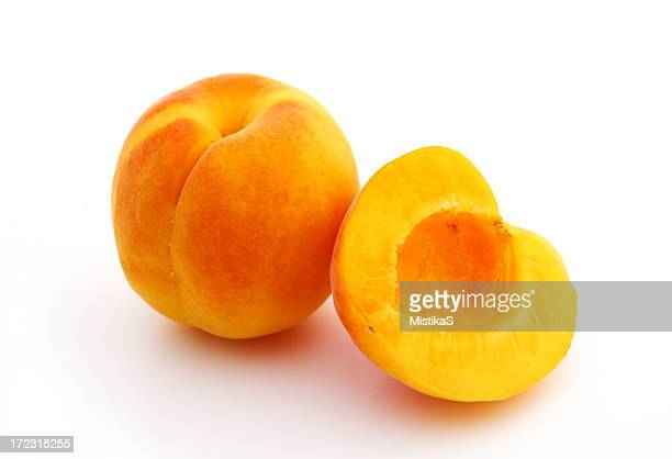 Yellow apricot and a sliced half over a white background