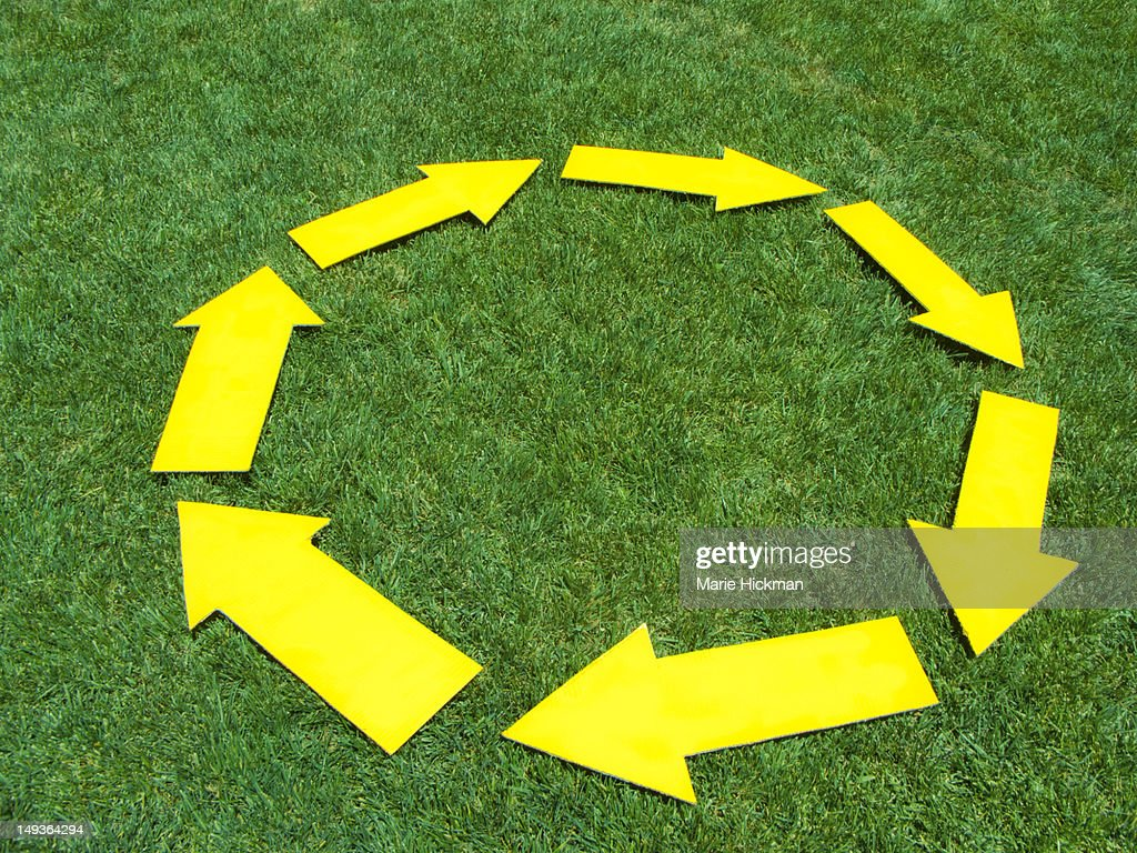 Yellow arrows forming a circle on the grass. : Stock Photo