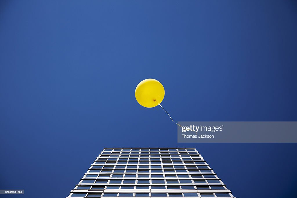 Yellow balloon floating past single skyscraper : Stock Photo