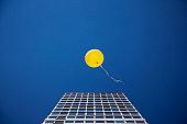 Yellow balloon floating past single skyscraper