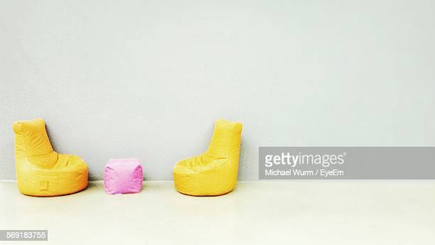 Yellow bean bags arranged against wall