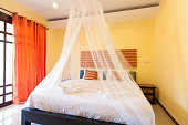 Contemporary bedroom with mosquito netting at Banana Garden Beach, Koh lanta, Krabi, Thailand.