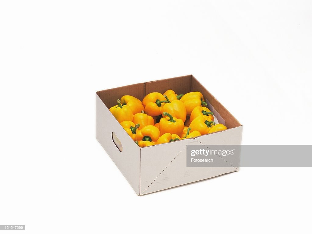 Yellow bell peppers in box, high angle view