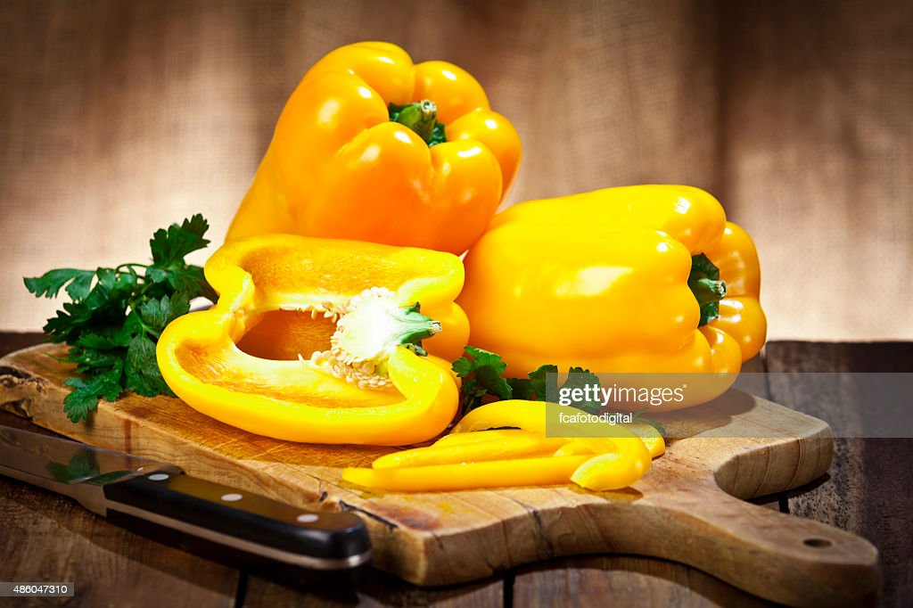 Yellow bell peppers on wooden cutting board