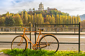 Yellow bicycle parked in a street that runs alongside the River Po in Turin (Piedmont, Italy). In the background the church and the monastery of Monte dei Cappuccini.