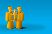 Yellow binoculars isolated on  a blue background