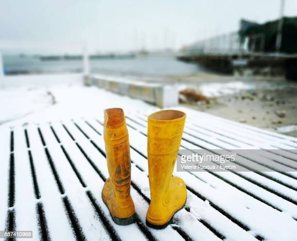 Yellow Boots On Snow Covered Bench