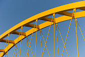 Fragment of a yellow bridge showing beams and cables against a steel blue sky shot in Utrecht, Netherlands