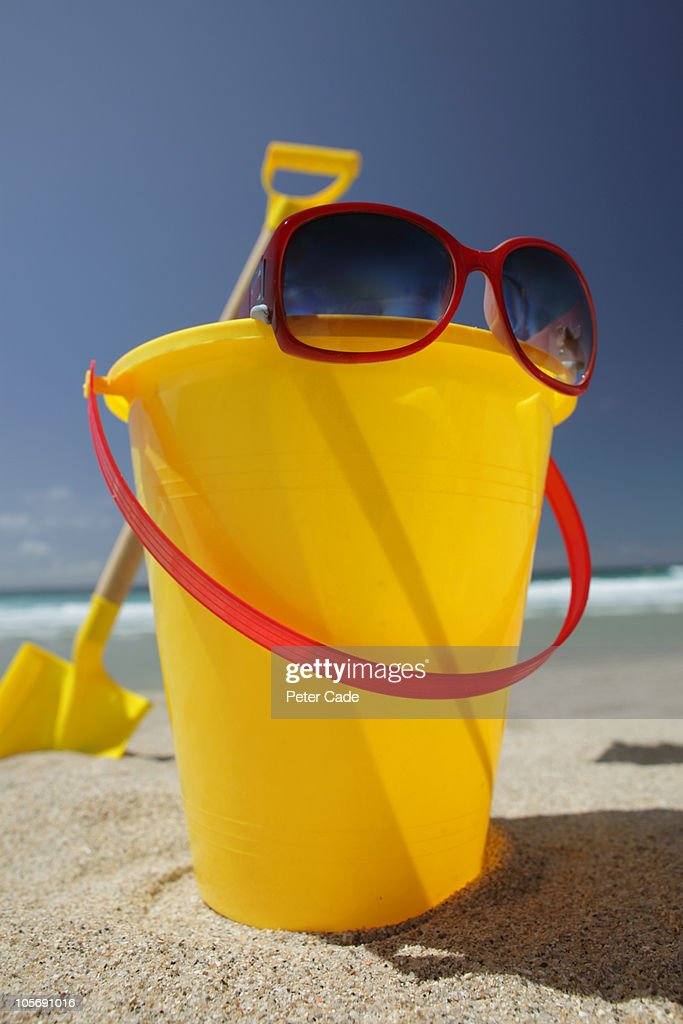 Yellow bucket and spade with red sunglasses by sea : Stock Photo