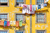 Picturesque yellow building facade with peeling paint and colorful clothes lines in historic Porto, Portugal.