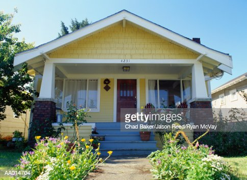 Yellow bungalow style house with garden, exterior view