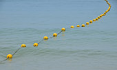 Yellow Buoy With Rope Floating On Sea