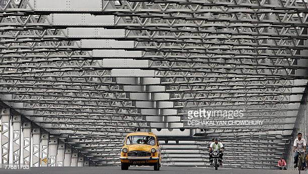 A yellow cab and a few two wheelers ply across the deserted Howrah Bridge in Kolkata 31 October 2007 during a call of state wide general strike by...