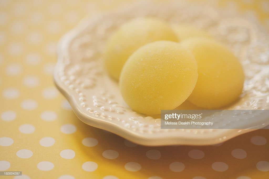 Yellow candies in dish : Stock Photo