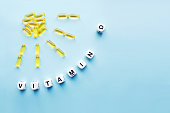 Yellow capsules in the form of the sun with rays and the word vitamin D from white cubes with letters on a blue background. VITAMIN D word for healthy and medical concept. Sunshine vitamin health bene