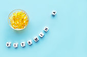 Yellow capsules in the round glass bowl and the word vitamin A from white cubes with letters on a blue background. healthy and medical concept. retinol, retinal, retinoic acid,  provitamin A, caroteno