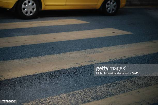 Yellow Car By Zebra Crossing On Street At Night