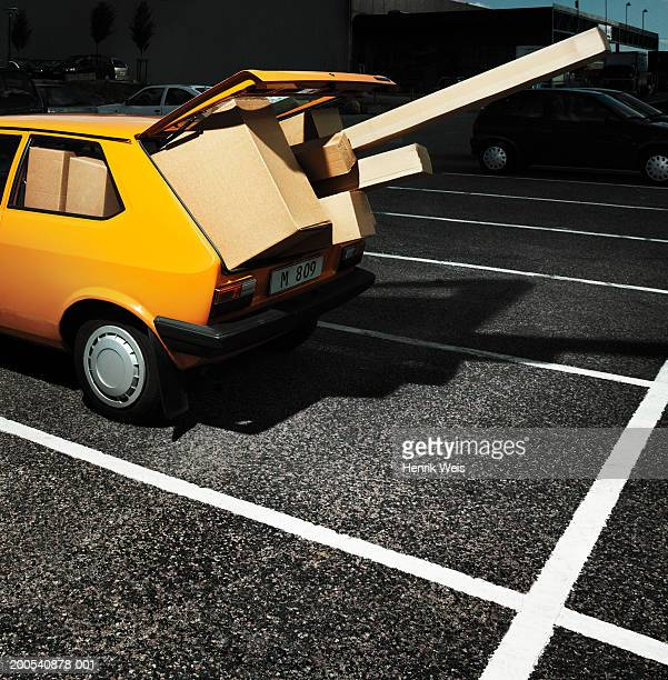 Yellow car in car park with open boot filled with packages